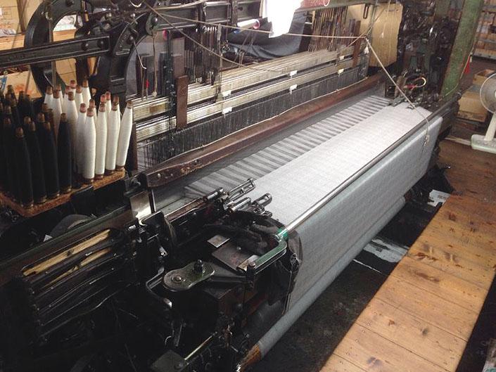 batak Clothはすべてこのショーンヘル式低速織機で織られています。ゆっくり織り上げ、タテ糸のストロークもたっぷりありますので、糸に膨らみと弾性がもたらされ、活き活きとした高級感のある服地が織り上がります。世界でもほとんど稼働していない旧式の織機です。